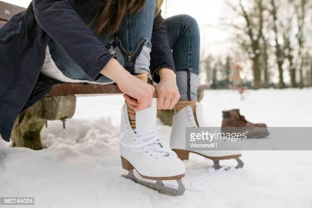 woman putting on her ice skates - schaatsen stockfoto's en -beelden
