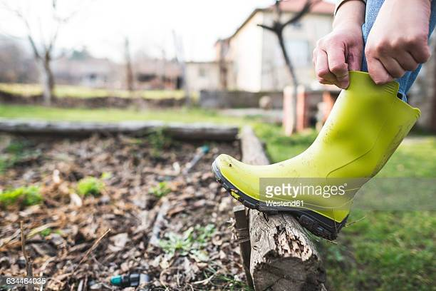 woman putting on her wellington boots in the garden, close-up - applying stock pictures, royalty-free photos & images