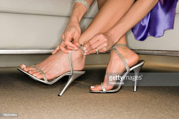 woman putting on high heel shoes - sandalia fotografías e imágenes de stock