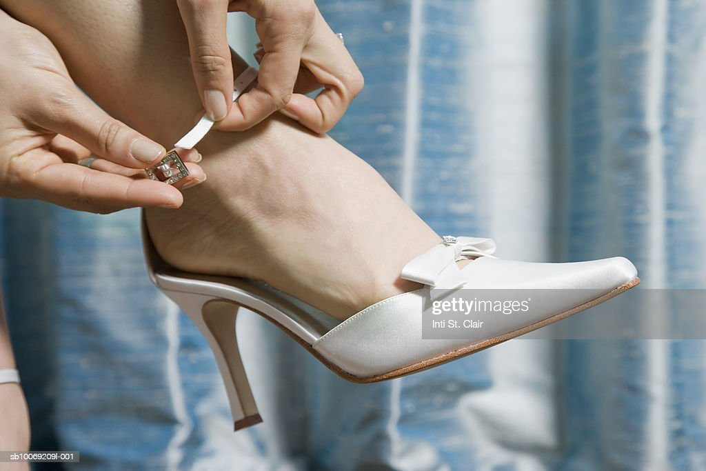 Woman putting on high heeled shoe, close up of foot : Stockfoto