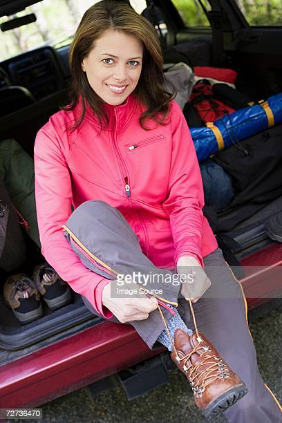 Woman putting on hiking boots