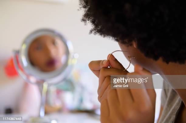 woman putting on hoop earring - earring stock pictures, royalty-free photos & images
