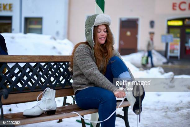 Woman putting on ice skates on a bench