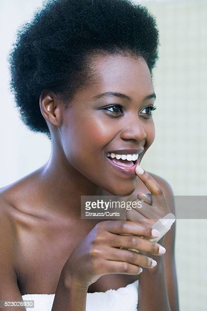 woman putting on lip balm - lip balm stock pictures, royalty-free photos & images