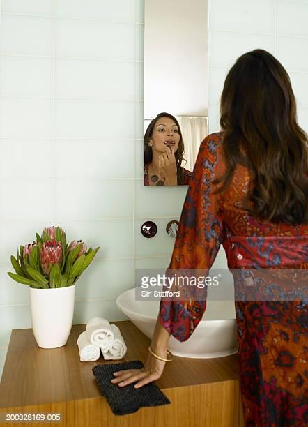 Woman putting on lipstick in bathroom