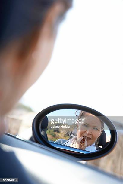 Woman putting on lipstick in car