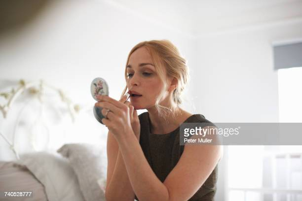 woman putting on lipstick with compact mirror - powder compact stock pictures, royalty-free photos & images