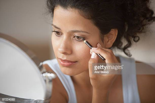 woman putting on make-up - eyeliner stock pictures, royalty-free photos & images