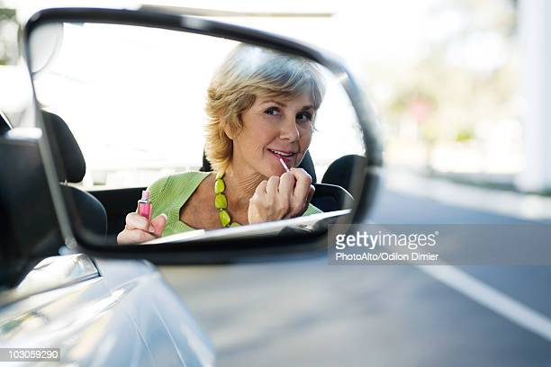 Woman putting on makeup, reflection in side-view mirror