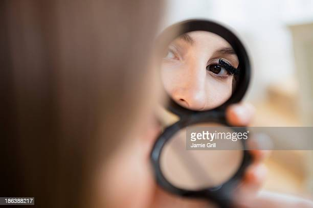 Woman putting on mascara in compact mirror