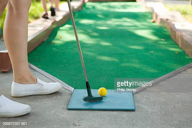 Woman putting on miniature golf course, low section, side view