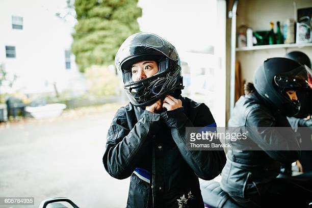 Woman putting on motorcycle helmet before ride