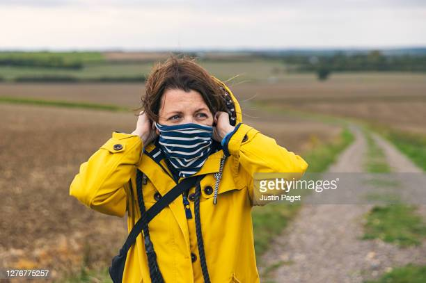 woman putting on neck gaiter in countryside - country road stock pictures, royalty-free photos & images