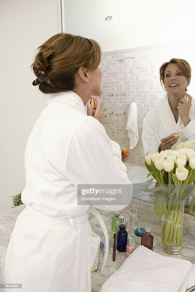 Woman putting on perfume : Stockfoto