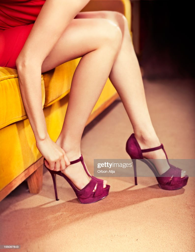 Woman putting on purple high heels : Stock Photo
