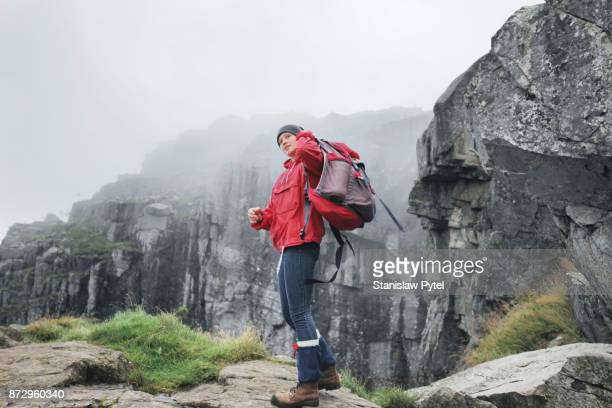 Woman putting on red backpack in mountains