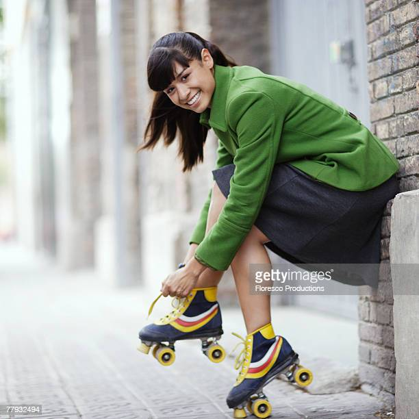 Woman putting on rollerskates outdoors
