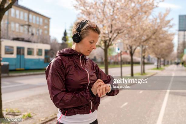woman putting on some music before an outdoor run - sweden stock pictures, royalty-free photos & images