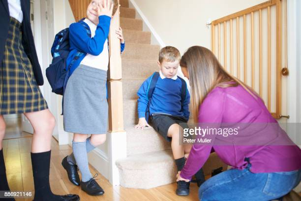 woman putting on sons school shoe on stairs - school girl shoes stock pictures, royalty-free photos & images