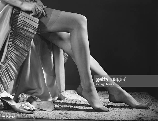 woman putting on stockings (b&w), low section - stocking feet stock photos and pictures