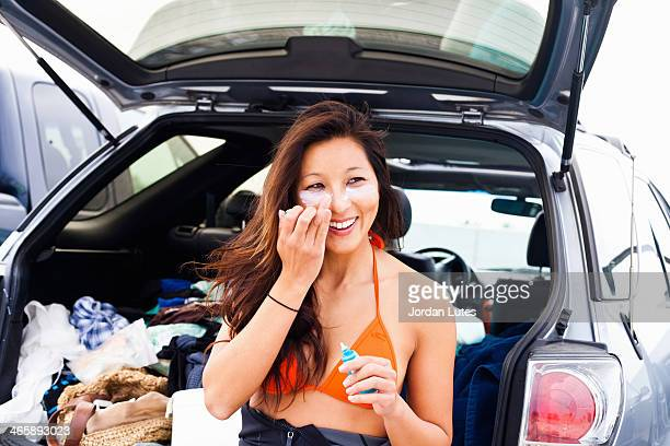 woman putting on suncream, hermosa beach, california, usa - sunscreen stock photos and pictures
