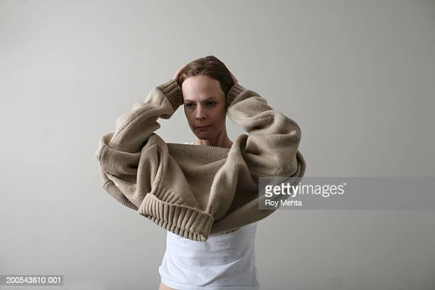 Woman putting on sweater