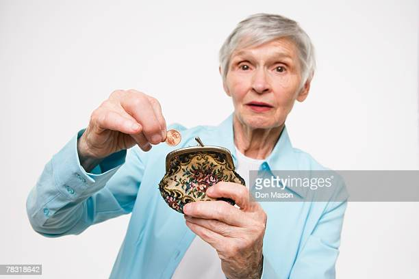 woman putting penny in coin purse - miserly stock pictures, royalty-free photos & images