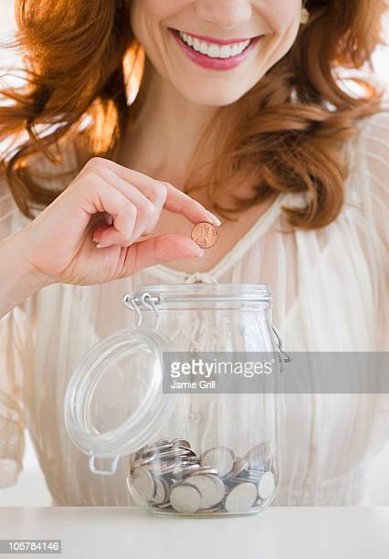 Woman putting penny in jar