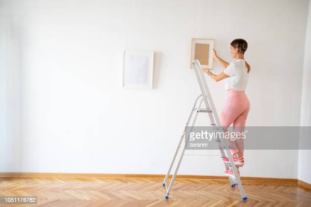 woman putting pictures on the wall - ladder stock pictures, royalty-free photos & images