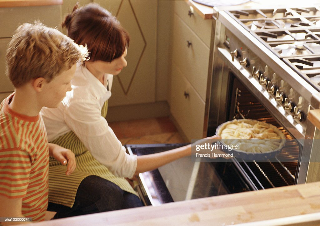 Woman putting pie in oven : Stockfoto