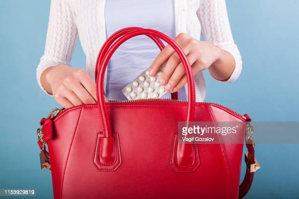 woman putting pills to red leather handbag - red leather purse stock pictures, royalty-free photos & images