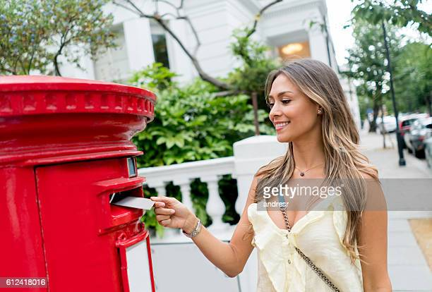 Woman putting postcard in the mailbox