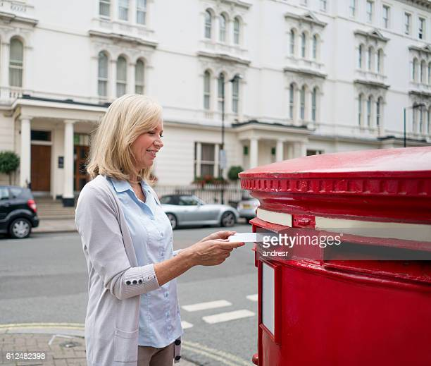 woman putting postcard in the mailbox - sending stock pictures, royalty-free photos & images