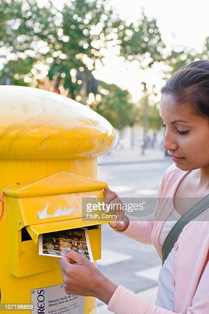 Woman putting postcard into letterbox