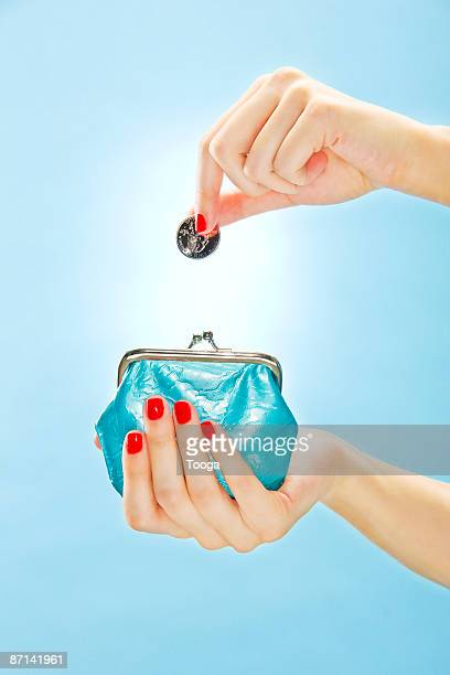 woman putting quarter in change purse - clutch bag stock pictures, royalty-free photos & images