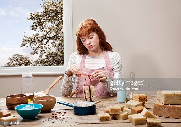 woman putting ribbon around soaps. - home made stock pictures, royalty-free photos & images
