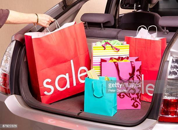 Woman putting sale carrier bag in car boot.