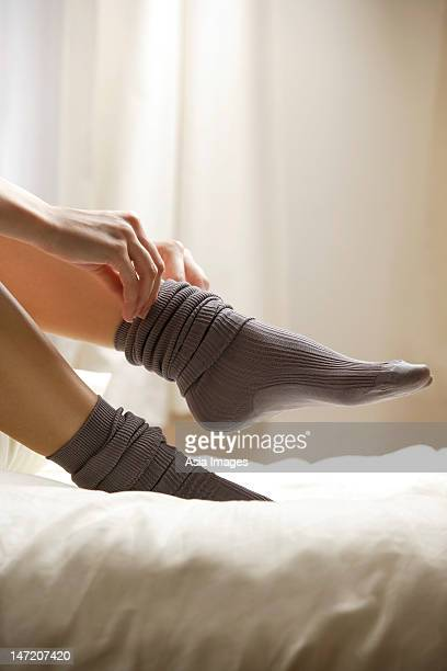 woman putting socks on feet