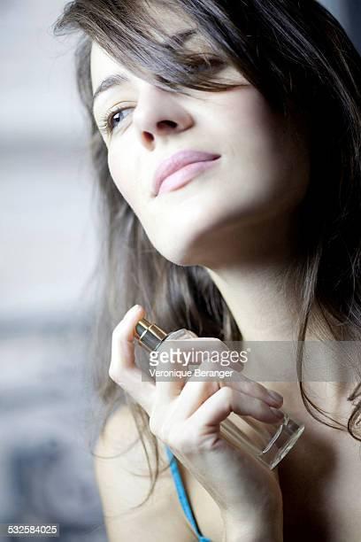 Woman putting some perfume on.