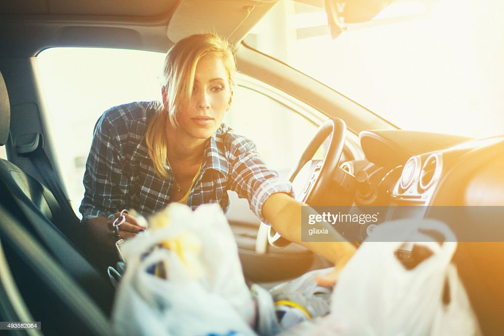 Woman putting some plastic bags into her car. : Stock Photo
