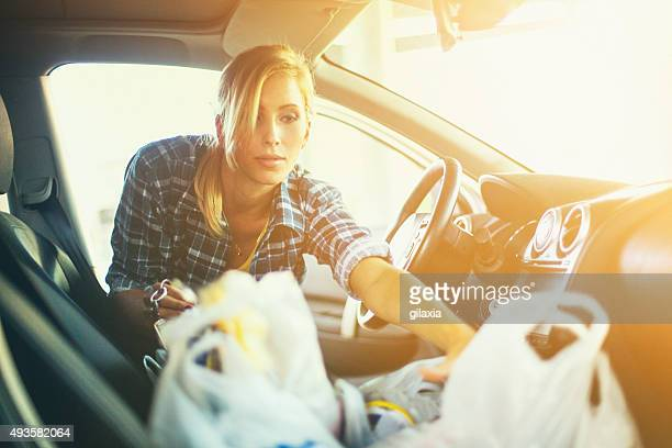 Woman putting some plastic bags into her car.