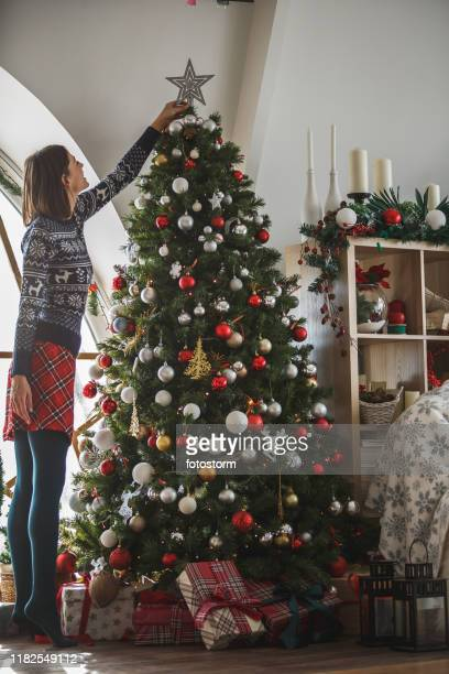 woman putting star on top of a christmas tree - tall high stock pictures, royalty-free photos & images
