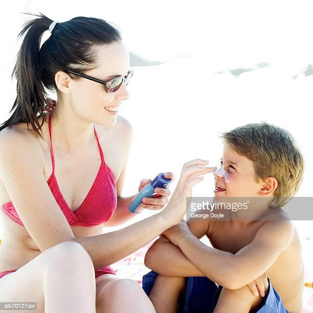 woman putting sun block on a boy's (6-8) nose