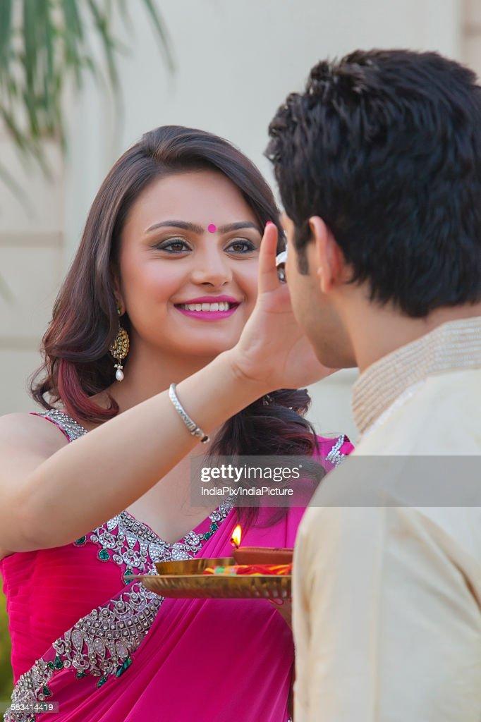 Woman putting tika on mans forehead : Stock Photo