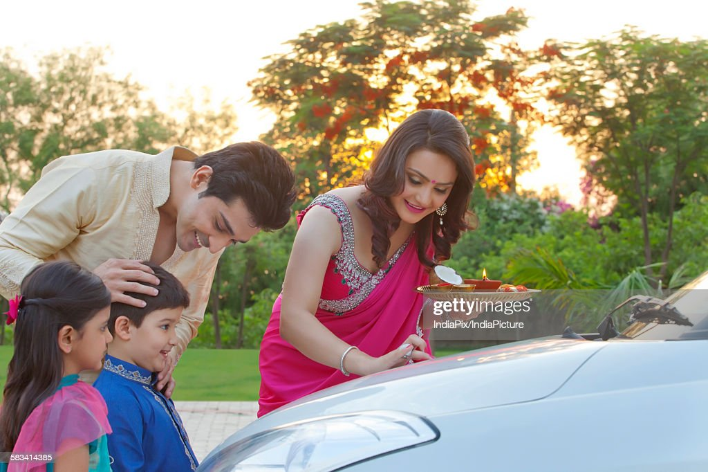 Woman putting tika on new car : Stock Photo