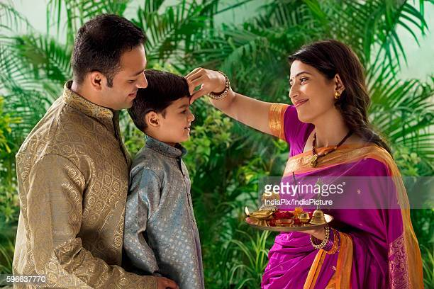 Woman putting tikka on her sons forehead