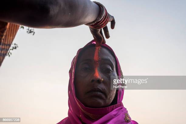 A woman putting tilak on her forehead after taking a holy dip into the river during the Chhath Puja festival in Kolkata West Bengal on october 26...