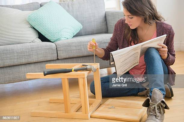 woman putting together stool - build grill stock photos and pictures