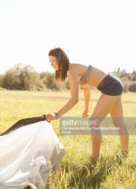 Woman putting up tent outdoors