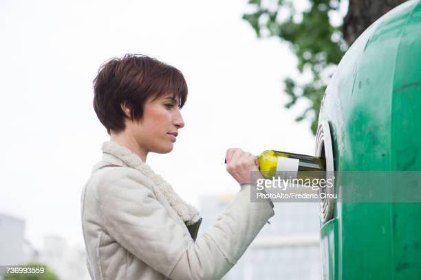 woman putting wine bottle into recycling bin - recipiente fotografías e imágenes de stock